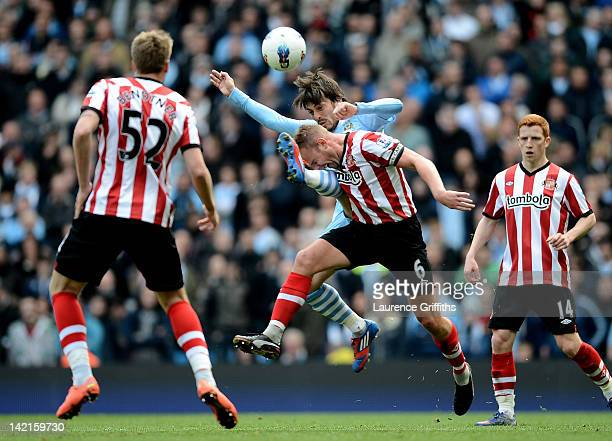 Lee Cattermole of Sunderland competes with David Silva of Manchester City during the Barclays Premier League match between Manchester City and...
