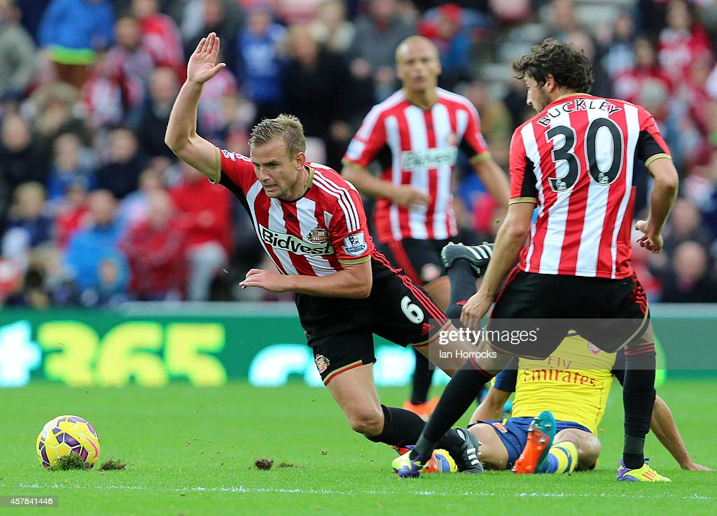 Lee Cattermole of Sunderland (L) is brought down by Keiran Gibbs of Arsenal (R) during the Barclays Premier League match between Sunderland AFC and Arsenal FC at The Stadium of Light on October 25, 2014 in Sunderland, England.