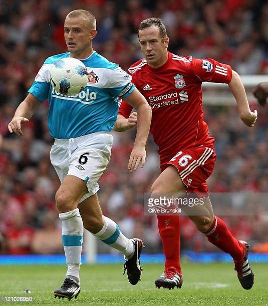 Lee Cattermole of Sunderland is challenged by Charlie Adam of Liverpool during the Barclays Premier League match between Liverpool and Sunderland at...