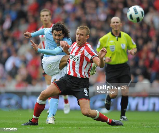 Lee Cattermole of Sunderland tries to block a shot by Carlos Tevez of Manchester City during the Barclays Premier League match between Sunderland and...