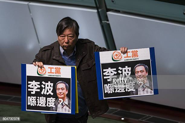 Lee Cheukyan chairman of the Labour Party holds signs protesting the disappearance of bookseller Lee Bo during the policy address of Hong Kong Chief...