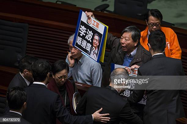 Lee Cheukyan chairman of the Labour Party third right stands surrounded by security officials as he holds signs protesting the disappearance of...