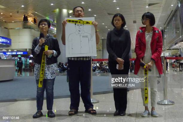 Lee Chingyu wife of jailed Taiwanese activist Lee Mingcheh stands with NGO workers during a press conference at Taoyuan International Airport in...