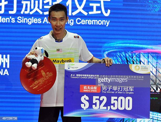 Lee Chong Wei of Malaysia poses with his trophy after the men's singles final match against Chen Long of China at the China Open badminton tournament...