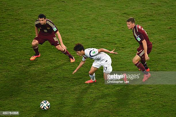 Lee ChungYong of South Korea controls the ball against Alan Dzagoev and Igor Denisov of Russia during the 2014 FIFA World Cup Brazil Group H match...