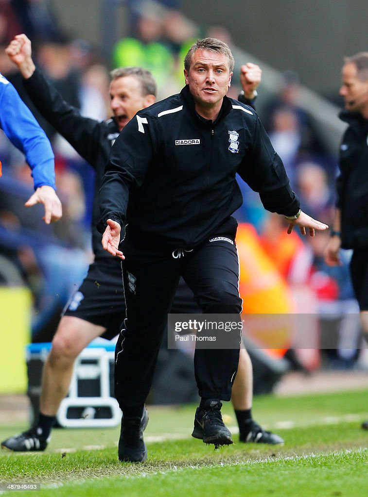 Lee Clark manager of Birmingham City celebrates with the team bench as they avoid relegation after the Sky Bet Championship match between Bolton Wanderers and Birmingham City at Reebok Stadium on May 3, 2014 in Bolton, England.