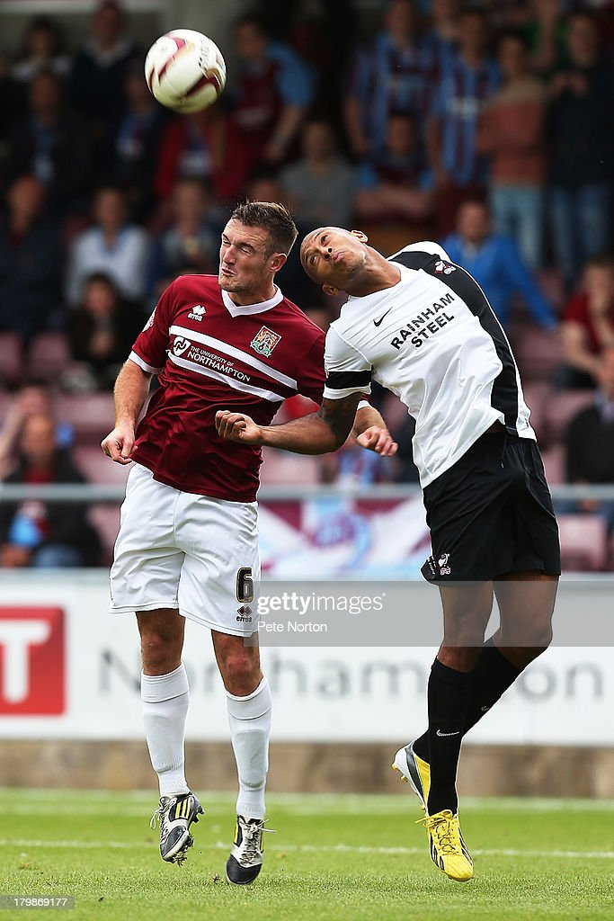Lee Collins of Northampton Town challenges for the ball with Chris Iwelumo of Scunthorpe United during the Sky Bet League Two match between Northampton Town and Scunthorpe United at Sixfields Stadium on September 7, 2013 in Northampton, England.