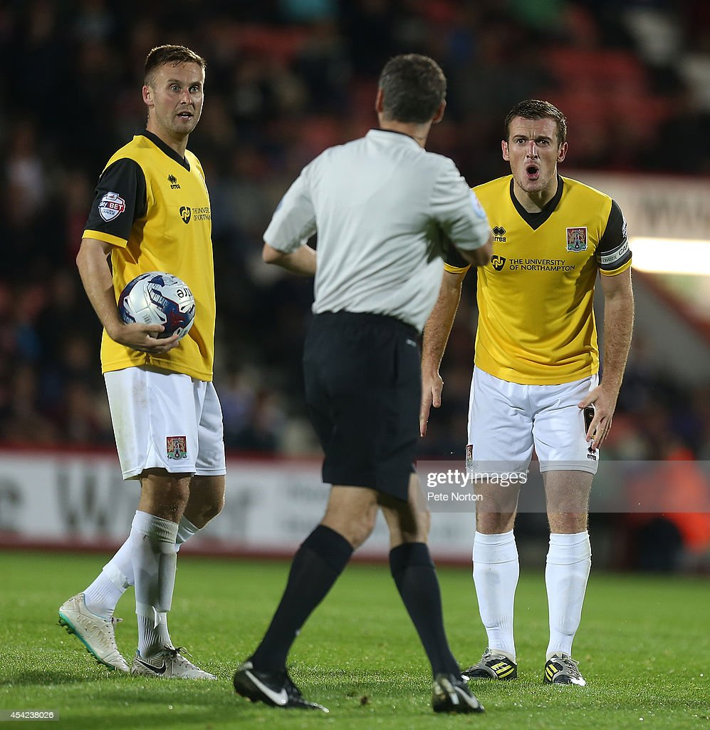 Lee Collins of Northampton Town makes his point to referee Carl Berry as team mate Joel Byrom looks on during the Capital One Cup Second Round match between AFC Bournemouth and Northampton Town at Goldsands Stadium on August 26, 2014 in Bournemouth, England.
