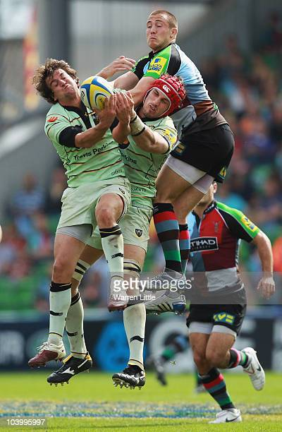 Lee Dickson and Christian Day of Northampton jump against Mike Brown of Harlequins for the ball during the Aviva Premiership match between Harlequins...