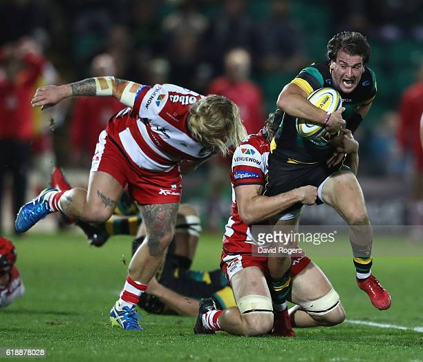 Lee Dickson of Northampton is held by Jacob Rowan during the Aviva Premiership match between Northampton Saints and Gloucester Rugby at Franklin's...