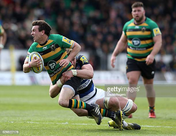 Lee Dickson of Northampton is tackled by David Denton during the Aviva Premiership match between Northampton Saints and Bath at Franklin's Gardens on...