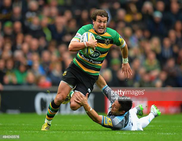 Lee Dickson of Northampton Saints weaves around a tackle from Mike Delany of Newcastle Falcons during the Aviva Premiership match between Northampton...