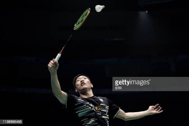 Lee Dongkeun of South Korea hits a return against Kento Momota of Japan during their men's singles first round match at the 2019 Badminton Asia...
