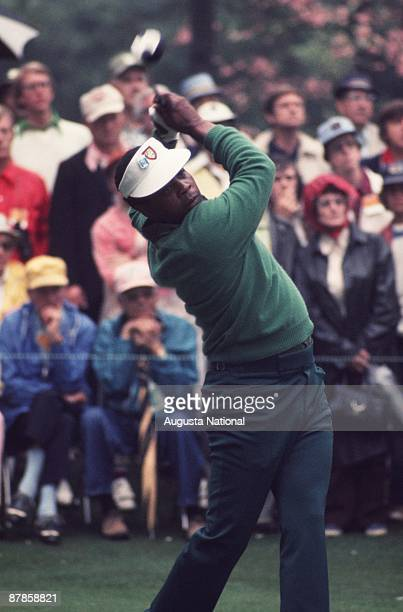 Lee Elder watches his shot from the finish position in front of a small gallery during the 1975 Masters Tournament at Augusta National Golf Club on...