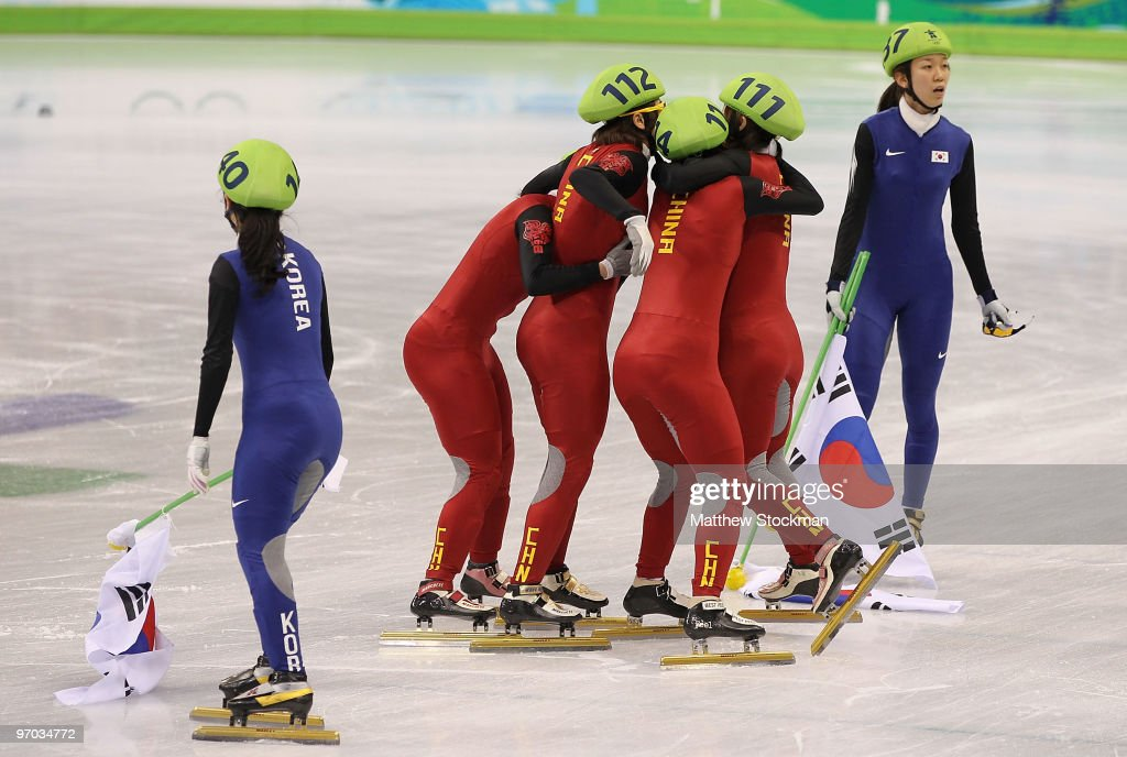Lee Eun-Byul (L) and Cho Ha-Ri (R) of South Korea looks on as (L-R) Zhang Hui, Wang Meng, Zhou Yang and Sun Linlin of China celebrate winning the gold medal, after Team Korea was disqualified, in the Short Track Speed Skating Ladies' 3000m relay finals on day 13 of the 2010 Vancouver Winter Olympics at Pacific Coliseum on February 24, 2010 in Vancouver, Canada.