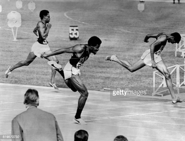 US Lee Evans crosses the finish line of the men's 400m final in 438 seconds ahead of compatriots Larry James and Ronald Freeman at the athletics...