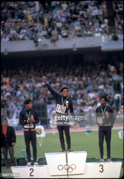 Lee Evans of the US smiles after receiving his gold medal for winning the 400m race while Larry James and Ronald Freeman look on at the Olympics in...