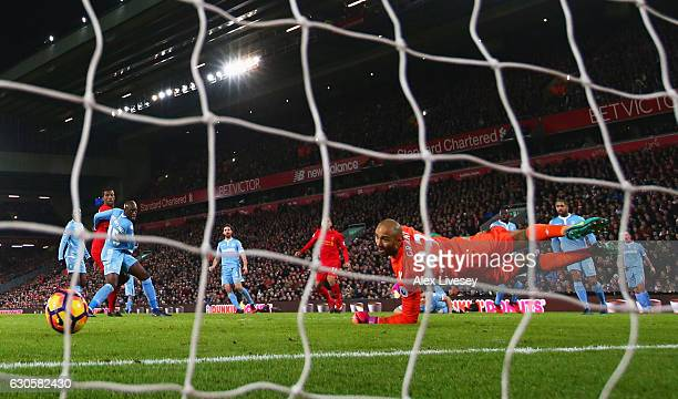 Lee Grant of Stoke City dives in vain as Roberto Firmino of Liverpool scores their second goal during the Premier League match between Liverpool and...