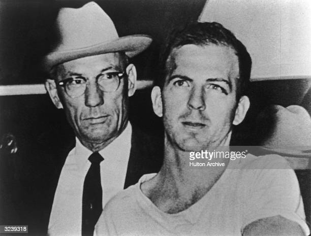 Lee Harvey Oswald alleged assassin of President John F Kennedy is detained by a police officer while under arrest Dallas Texas November 1963