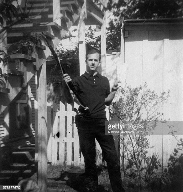 Lee Harvey Oswald holds a MannlicherCarcano rifle and a newspaper in a backyard This photograph is one of the controversial backyard photos used in...