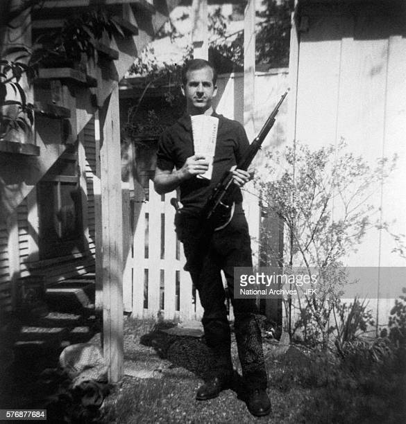 Lee Harvey Oswald holds a MannlicherCarcano rifle and newspapers in a backyard This photograph is one of the controversial backyard photos used in...