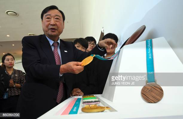 Lee HeeBeom president of the PyeongChang Organising Committee for the 2018 Olympic Games shows the PyeongChang 2018 Olympic gold medal during its...