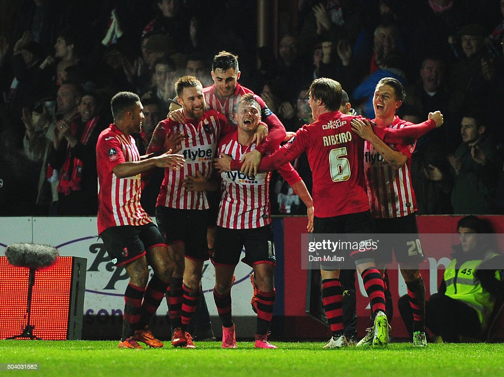 Lee Holmes of Exeter City (C) celebrates with team mates as he scores their second goal during the Emirates FA Cup third round match between Exeter City and Liverpool at St James Park on January 8, 2016 in Exeter, England.
