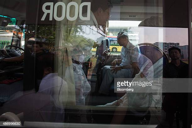 Lee Hsien Loong Singapore's prime minister and leader of the People's Action Party sits on a bus while supporters are reflected on the window in...