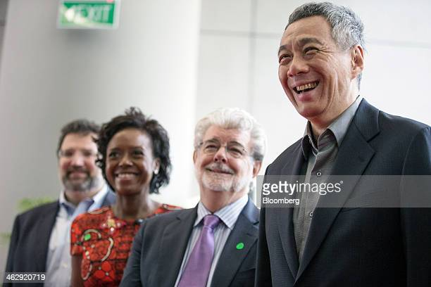 Lee Hsien Loong Singapore's prime minister right and billionaire George Lucas filmmaker and founder of Lucasfilm Ltd second right react during the...
