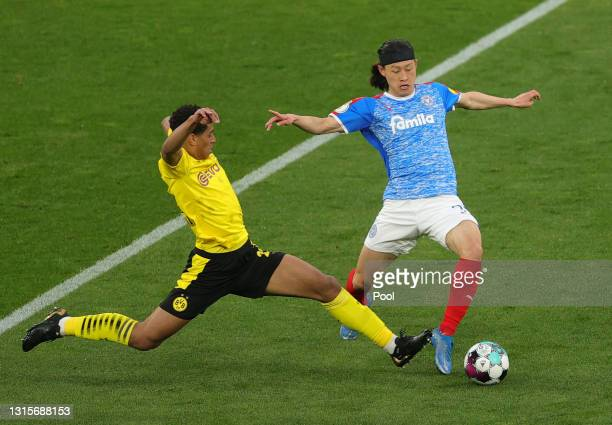 Lee Jae-Song of Holstein Kiel is challenged by Jude Bellingham of Borussia Dortmund during the DFB Cup semi final match between Borussia Dortmund and...