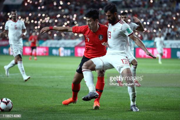 Lee JeongHyeop of South Korea competes for the ball with Mohammad Hossein Kanani Zadegan of Iran during the international friendly match between...