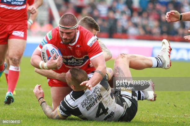 Lee Jewitt of Hull KR is tackled by Josh Griffin and Jamie Shaul of Hull FC during the BetFred Super League match between Hull KR and Hull FC at KCOM...