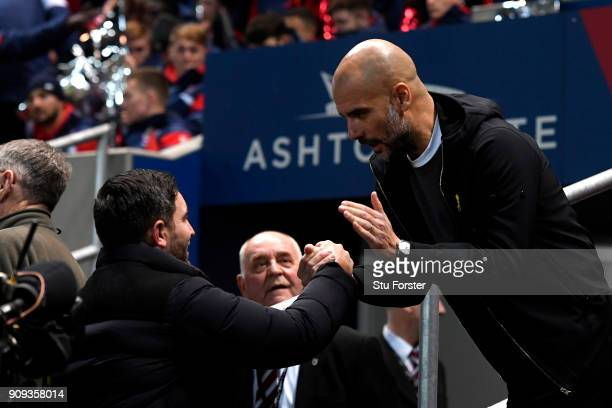 Lee Johnson manager of Bristol City and Josep Guardiola Manager of Manchester City shake hands prior to the Carabao Cup semifinal second leg match...