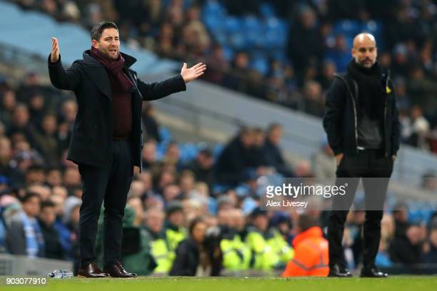 Lee Johnson manager of Bristol City reacts as Josep Guardiola Manager of Manchester City looks on during the Carabao Cup SemiFinal First Leg match...