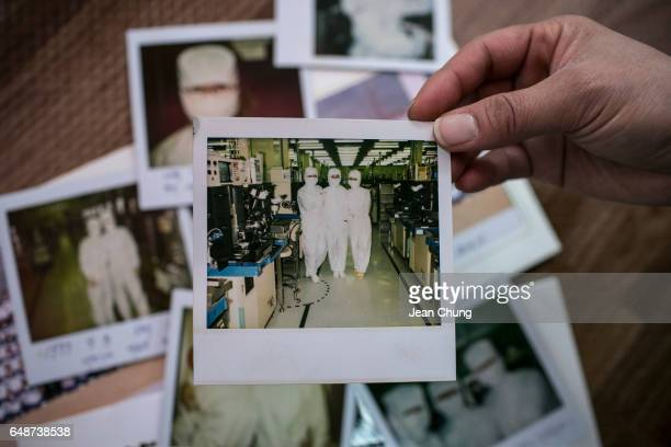 Lee Jongran at right a labor attorney for Supporters for Health and Right of People in Semiconductor Industry holds a polaroid picture of a former...