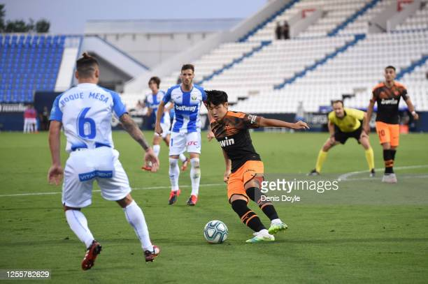 Lee Kang-In of Valencia battles for possession with Roque Mesa of Leganes during the Liga match between CD Leganes and Valencia CF at Estadio...