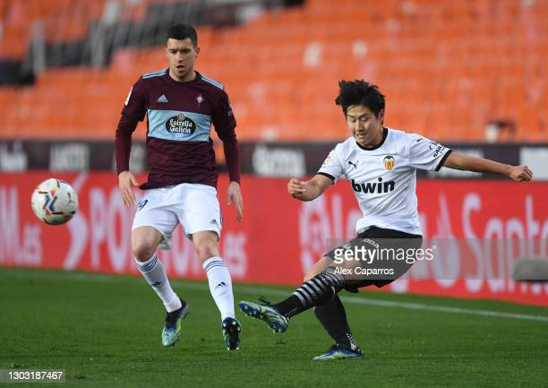 Lee Kang-In of Valencia CF crosses the ball under pressure from Aaron Caricol of Celta Vigo during the La Liga Santander match between Valencia CF...
