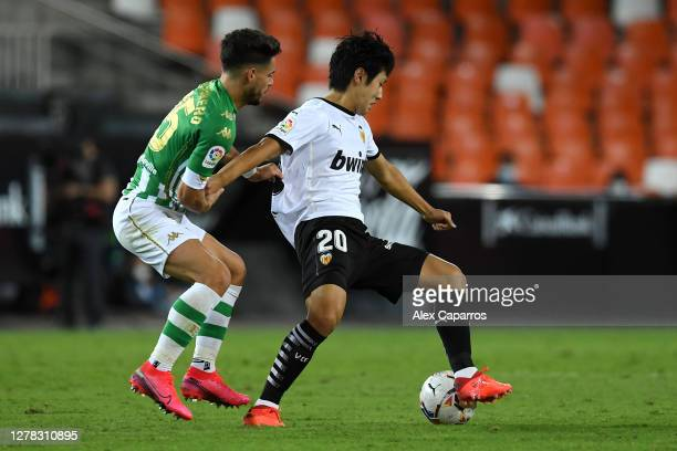 Lee Kang-In of Valencia CF is challenged by Alex Moreno of Real Betis during the La Liga Santander match between Valencia CF and Real Betis at...