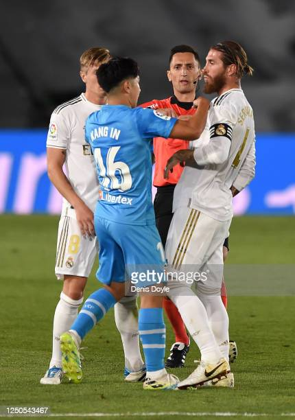 Lee Kang-In of Valencia CF is shown a red card by referee José María Sánchez Martínez after a tackle on Sergio Ramos of Real Madrid CF during the...