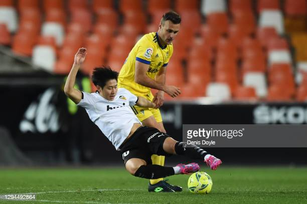 Lee Kang-In of Valencia is challenged by Cala of Cadiz CF during the La Liga Santander match between Valencia CF and Cadiz CF at Estadio Mestalla on...