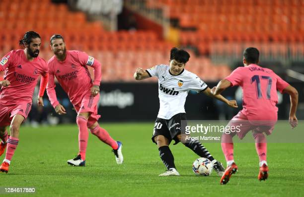 Lee Kang-In of Valencia is closed down by Isco and Lucas Vazquez of Real Madrid during the La Liga Santander match between Valencia CF and Real...