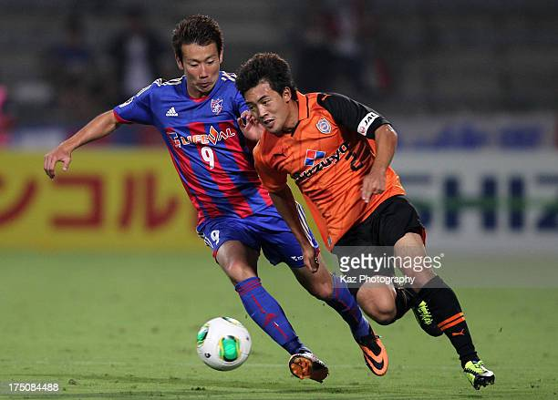 Lee Kije of Shimizu SPulse competes for the ball with Kazuma Watanabe during the JLeague match between Shimizu SPulse and FC Tokyo at IAI Stadium...