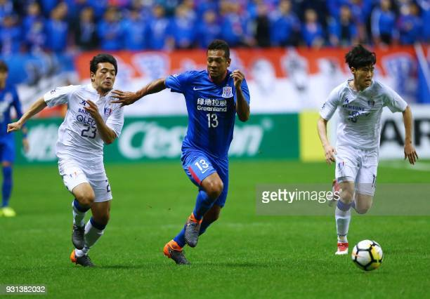 Lee Kije of Suwon Samsung Bluewings fights for the ball with Fredy Guarin of Shanghai Shenhua during the AFC Champions League group stage football...