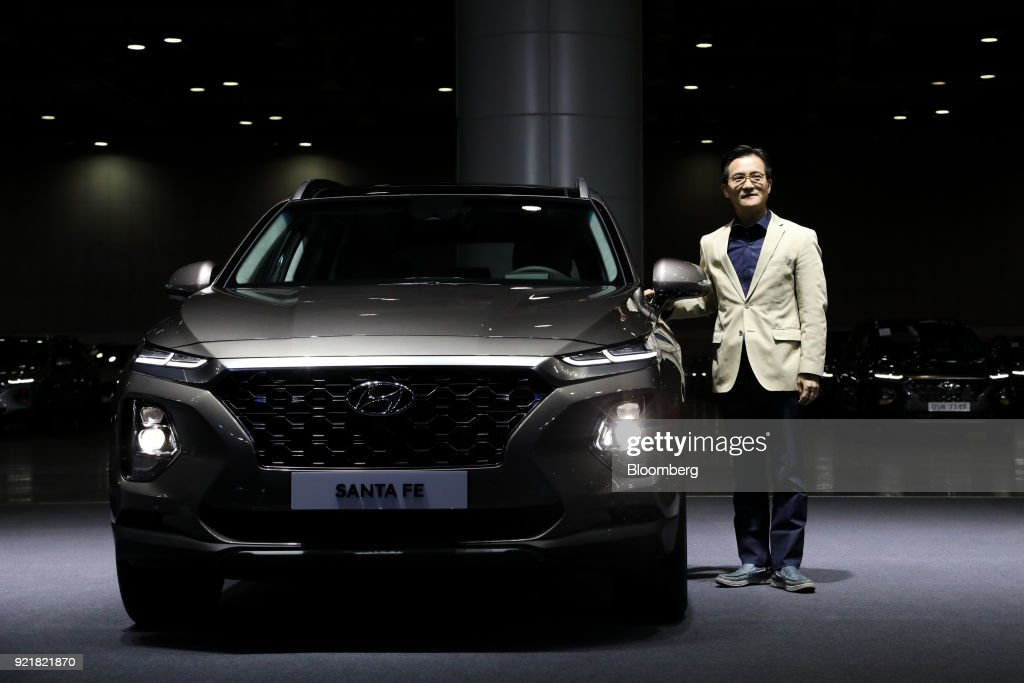 Lee Kwang-guk, executive vice president at Hyundai Motor Co., poses for a photograph next to a Hyundai Motor Co. Santa Fe sport utility vehicle (SUV) during a launch event for the updated vehicle in Goyang, South Korea, on Wednesday, Feb. 21, 2018. To recapture buyers in the U.S. who have shunned its sedans and compact cars, Hyundai has said it will bring eight new or redesigned crossovers or SUVs by 2020. Photographer: SeongJoon Cho/Bloomberg via Getty Images