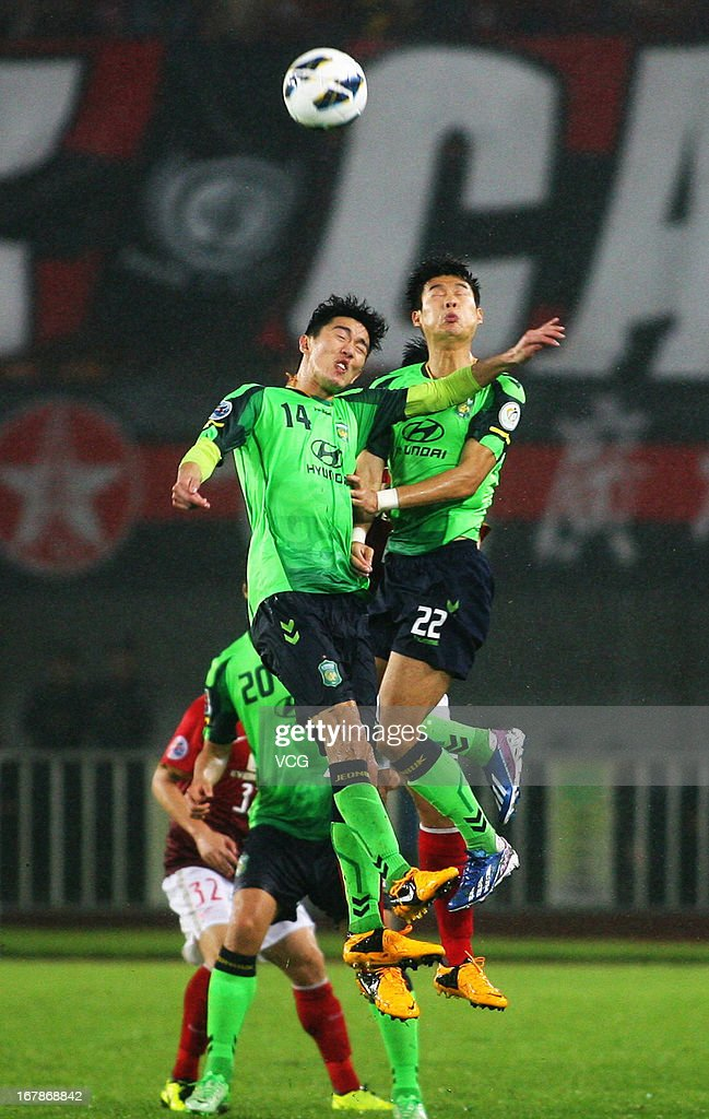 Lee Kyu-Ro #22 and Kim Jung-Woo #14 of Jeonbuk Hyundai Motors jump to head the ball during the AFC Champions League match between Guangzhou Evergrande and Jeonbuk Hyundai Motors at Tianhe Sports Center on May 1, 2013 in Guangzhou, China.