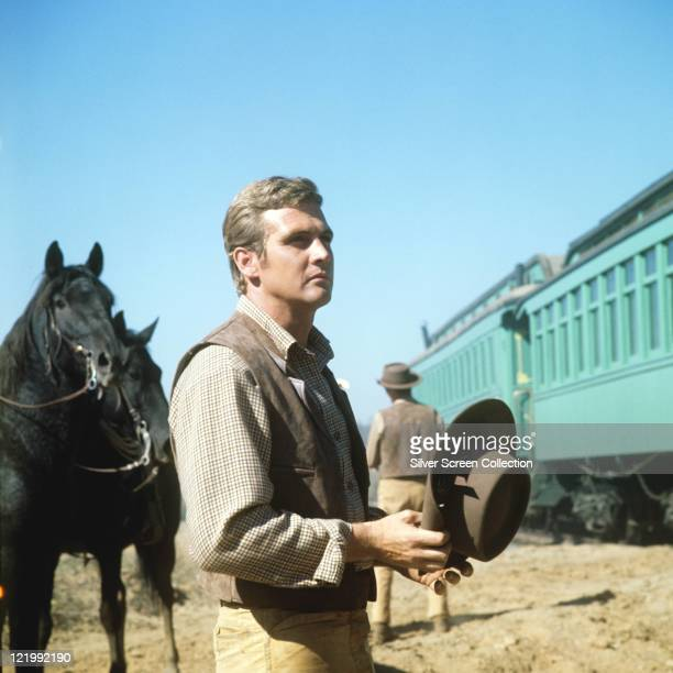 Lee Majors US actor holding a brown cowboy hat standing in front of blue train with two black horses behind him in a portrait issued as publicity for...