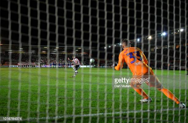 Lee Martin of Exeter City scores the winning penalty past Bartosz Bialkowski of Ipswich Town during the Carabao Cup First Round match between Exeter...