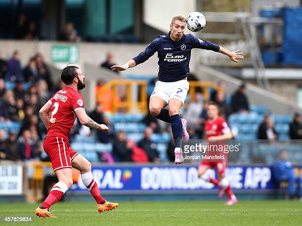 Lee Martin of Millwall jumps to head a ball under pressure from John Brayford of Cardiff during the Sky Bet Championship match between Millwall and...