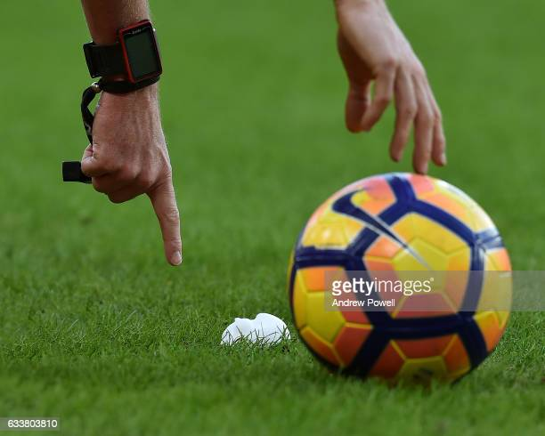 Lee Mason referee points at here the Premier league ball should be during the Premier League match between Hull City and Liverpool at KCOM Stadium on...