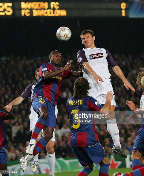 Lee McCulloch of Rangers goes for a high ball against Eric Abidal of Barcelona during the UEFA Champions League Group E match between Barcelona and...